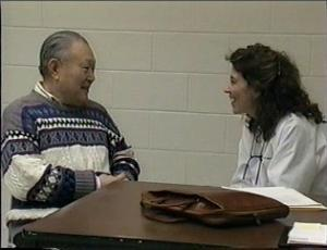 Man in sweater talking to female doctor