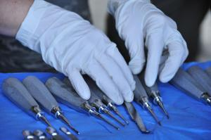 Hands with white gloves arranging dental tools