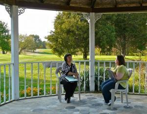 Two women sitting in chairs in an outdoor gazebo