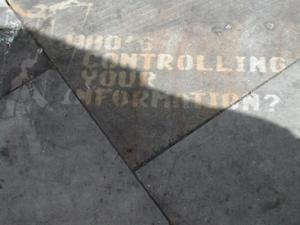 "Photo of graffiti on the ground that says ""Who's controlling your information?"""