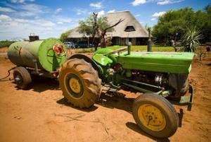 Image of a dusty tractor hitched to a water tanker on a dirt field
