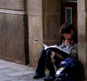 student with backpack sits and reads