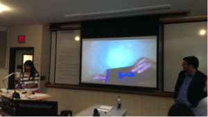 Female student giving lecture with overhead screen