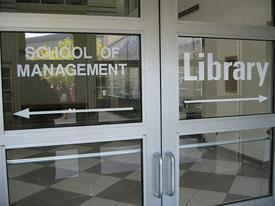Photo of glass door with School of Management to the left and Library to the right
