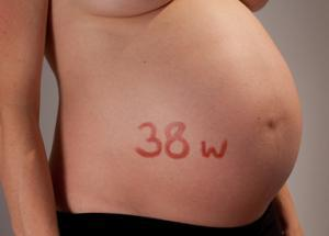 Exposed pregnant stomach with the text 38 w written on the stomach