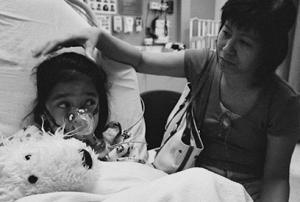 child wears a respirator in a hospital bed while woman looks on