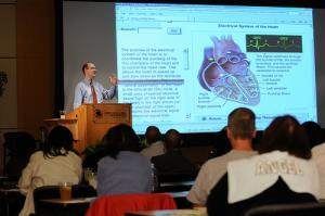 lecturer stands at podium gesturing in front of a screen depicting a heart while students look on