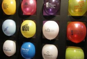 Multi-colored balloons with different hospital logos arranged in grid