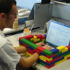 Person typing on laptop with Lego wall around it