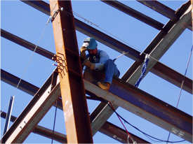 Construction worker on I beam structure